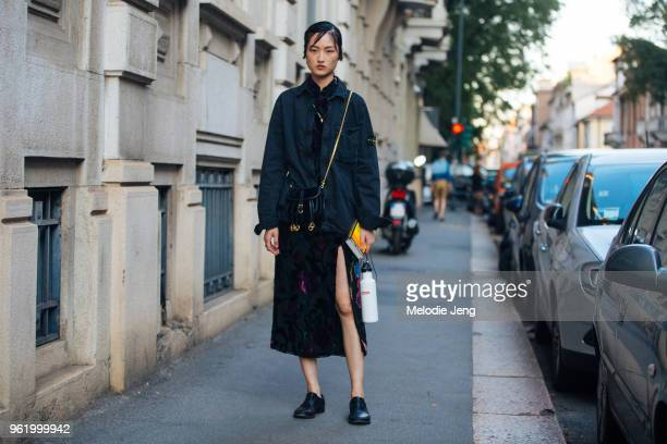 Model Jing Wen wears a black Stone Island jacket black Chloe purse black slit floral dress black shoes and a white Supreme water bottle after the...