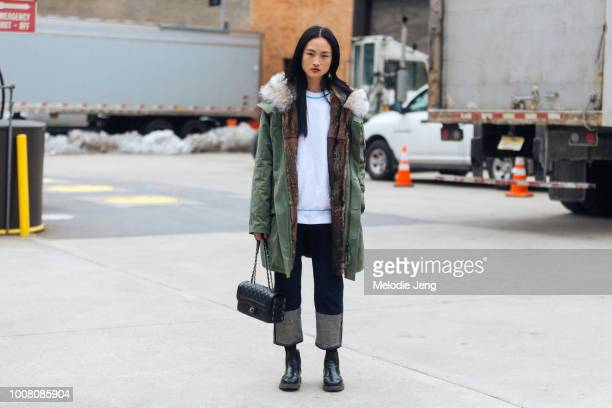 Model Jing Wen wears green parka with fur lining white top black Chanel bag and open hem jeans on Day 5 of New York Fashion Week Fall/Winter 2017 on...
