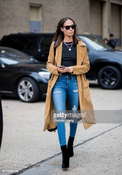 Model Joan Smalls wearing brown trench coat blue ripped denim jeans black ankle boots seen outside Ralph Lauren on February 12 2018 in New York City