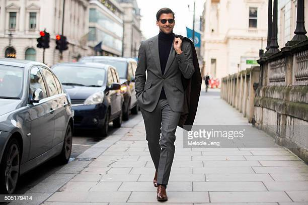 Model Johannes Huebl attends the Pringle of Scotland show in a gray Marc Anthony tailoring suit and coat black Brunello Cucinelli turtleneck and...