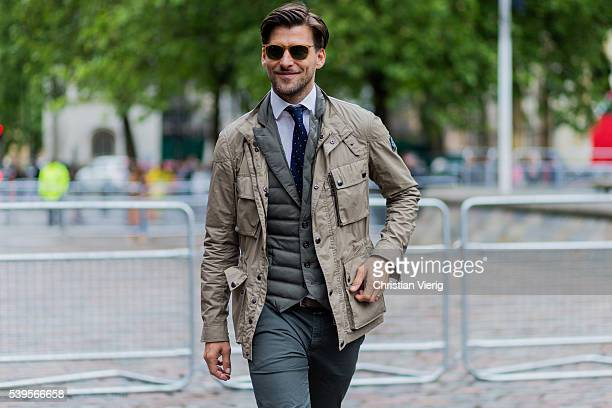 Model Johannes Huebl wearing a beige jacket and olive puffy jacket outside Belstaff during The London Collections Men SS17 on June 12 2016 in London...