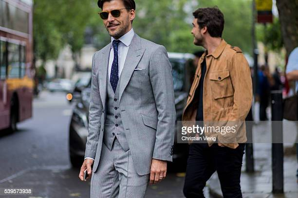 Model Johannes Huebl wearing a grey suit vest and tie and Robert Konjic outside Christopher Raeburn during The London Collections Men SS17 on June 12...