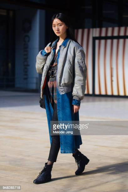 Model Joony Kim wears a light gray bomber jacket over a long denim jacket and a plaid shirt with a black beld during London Fashion Week February...