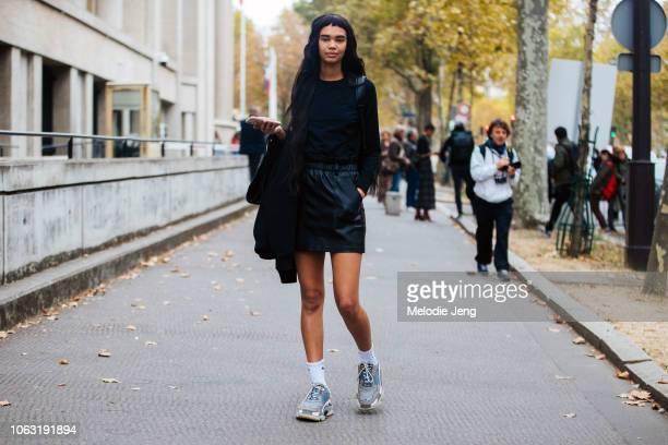 Model Jordan Daniels wears a black top black leather skirt white Nike socks and blue Balenciaga sneakers after the Miu Miu show during Paris Fashion...