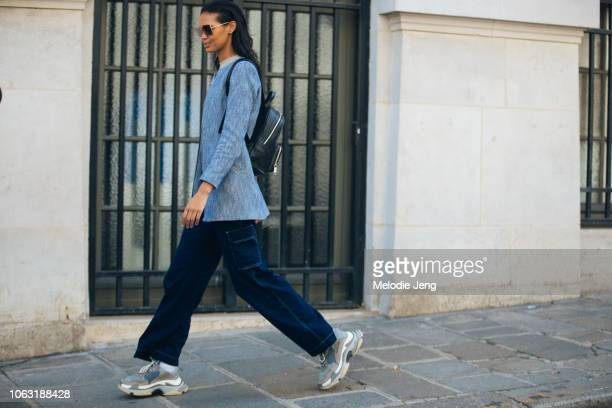 Model Jordan Daniels wears square sunglasses a blue jacket blue pants black leather backpack and blue Balenciaga sneakers after the Altuzarra show...