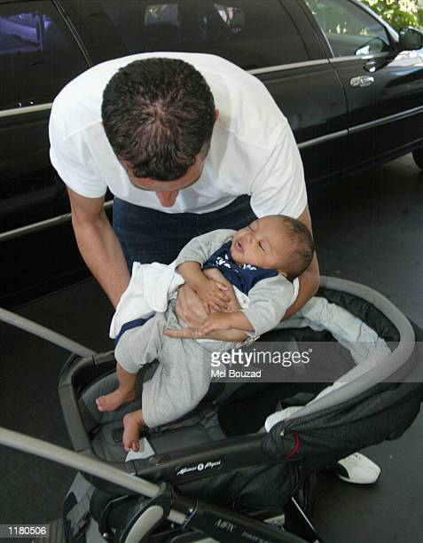 Model Jordan's baby Harvey is placed on his carriage by an assistant at the Los Angeles International Airport on July 29 2002 in Los Angeles...