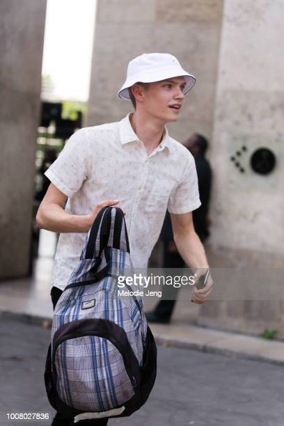 Model Jordy Gerritsma wears a white bucket hat white buttonup patterend shirt and a blue Vans backpack during Paris Fashion Week Men's Spring/Summer...