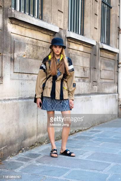Model Josefine Lynderup wears a black lala Berlin bucket hat, Ganni jacket, blue print dress, black Birkenstock sandals after the Valentino show...