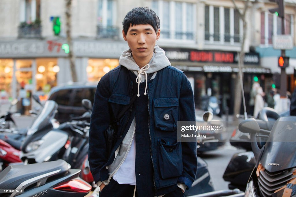 Model Joseph Kim wears a blue Stone Island jacket with