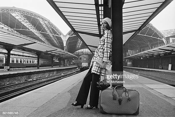 Model Judi Smith at Victoria Station wearing a charcoal and grey checked trenchcoat and charcoal jersey trousers by Gladrags, along with a white...