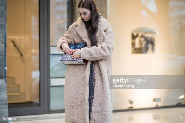 Model Julia Leineweber opening her bag wearing a HM teddy coat Mango bag Adidas jogger pants Zara sweater HM boots Gucci scarf on December 11 2017 in...