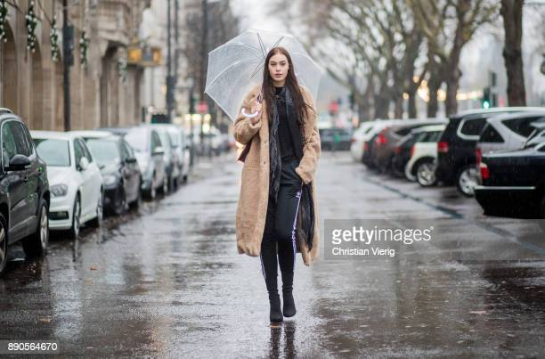 Model Julia Leineweber under an umbrella wearing a HM teddy coat Mango bag Adidas jogger pants Zara sweater HM boots Gucci scarf on December 11 2017...