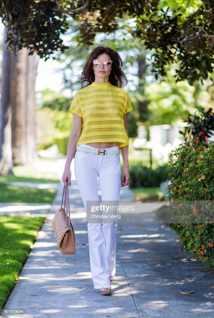 Model Julia Lescova wearing white jeans Rag&Bone, French Mauve yellow striped top, Chloe shoes, Celine sunglasses, Chanel bag on April 21, 2017 in Los Angeles, California.