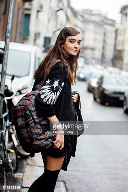 Model Julia Ratner wears wears a black sweater with prints on the sleeves, carries a colorful Dakine backpack, and keeps her hair in a wavy side-part...