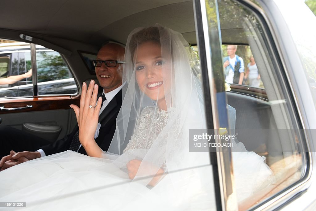 Model Julie Hantson shows her engagement ring as she leaves Cap Ferret's town hall with her father after her wedding with French singer Pascal Obispo on September 19, 2015.
