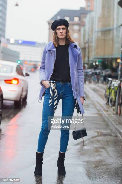 Model Julier Bugge wears a black beret a purple fur bomber jacket black sweater blue jeans a scarf on her waist black booties and a black YSL purse...
