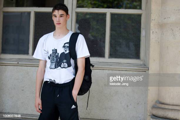 Model Kaito Defoort wears a white tshirt with a robot and Adidas black shorts during Paris Fashion Week Men's Spring/Summer 2018 on June 22 2017 in...