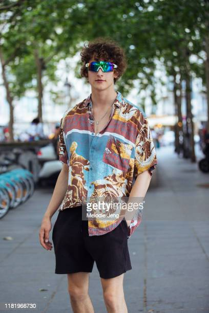 Model Kajus Valciukas wears reflective sunglasses a graphic buttonup shirt and black shorts after the Ludovic de Saint Sernin show during Paris...