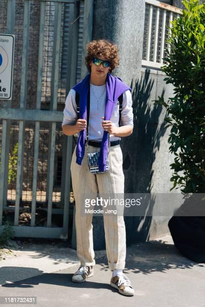 Model Kajus Valciukas wears reflective sunglasses, a purple sweatshirt on his neck, gray top, Cross necklace, Dior bag, tweed tan pants, and brown...