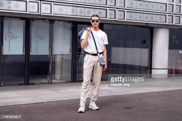 Model Kajus Valciukas wears reflective sunglasses, a white Dior t-shirt, Dior man bag, tan tweed pleated pants, and white Converse J.W. Anderson...
