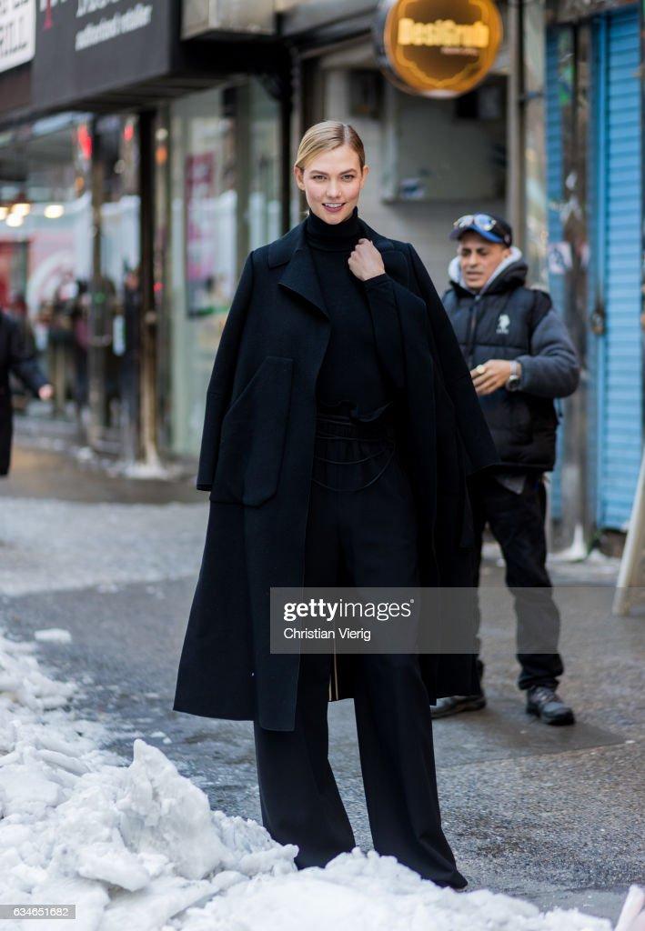 Model Karlie Kloss wearing a black coat, black turtleneck, black jogger pants outside Calvin Klein on February 10, 2017 in New York City.