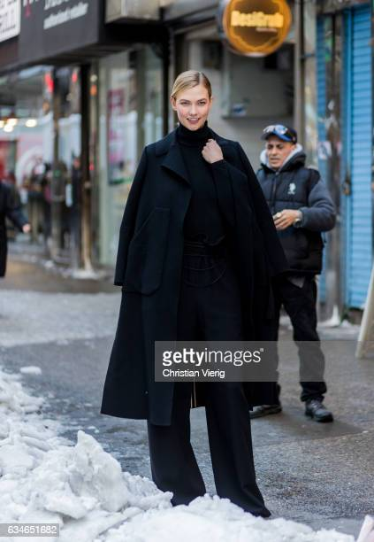 Model Karlie Kloss wearing a black coat black turtleneck black jogger pants outside Calvin Klein on February 10 2017 in New York City
