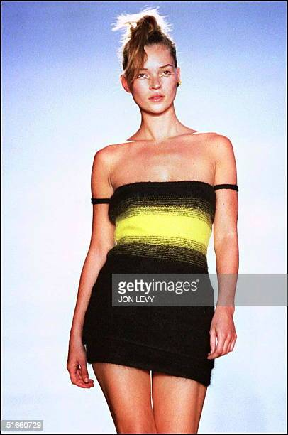 Model Kate Moss wears a black and yellow wool top over a black jersey knit skirt in the showing of Gianni Versace's Fall 1997 Versus fashion...