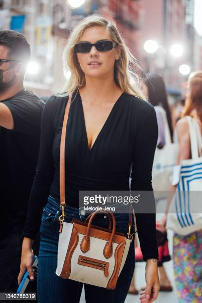 Model Kate Upton wears black sunglasses, a black top, blue jeans, and a Celine bag after the Tory Burch show on September 12, 2021 in New York City.
