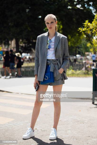 Model Kateryna Zub wears a plaid gray blazer and skirt blue paperclip bag and white sneakers during Couture Fall/Winter 2018 Fashion Week on July 3...