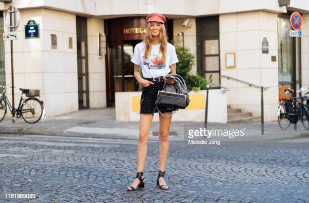 Model Kateryna Zub wears an orange conductor cap, white car t-shirt, black skirt, and black heels after the Zuhair Murad show during Couture Fashion...