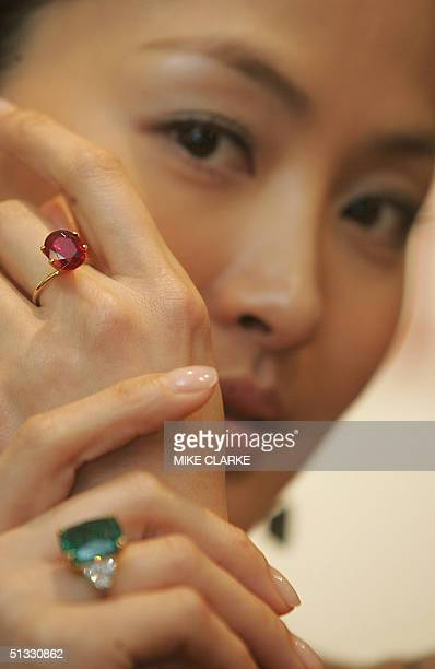 Model Kathy Chow poses with a 1621 carat cushionshaped Colombian emerald ring estimated at 34 million HKD and an 803 carat ovalcut Burmese ruby ring...