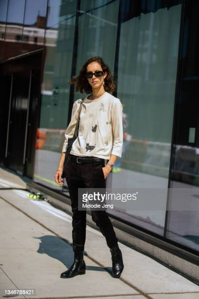 Model Katie Johnson wears black sunglasses, a white shirt with cats, black skinny pants, and black boots after the Khaite show on September 12, 2021...