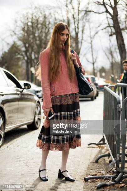 Model Kay Smetsers wearsr a pink suede jacket, quilted-styled vintage-style skirt, white tights, and black ballerina shoes after the Miu Miu show...