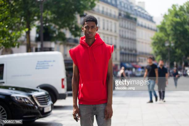 Model Keiron Caynes wears a red sleeveless hoodie during Paris Fashion Week Men's Spring/Summer 2018 on June 22 2017 in Paris France