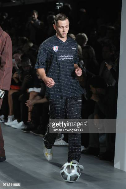 A model kicks a football on the runway at the What We Wear show during London Fashion Week Men's June 2018 at the BFC Show Space on June 11 2018 in...