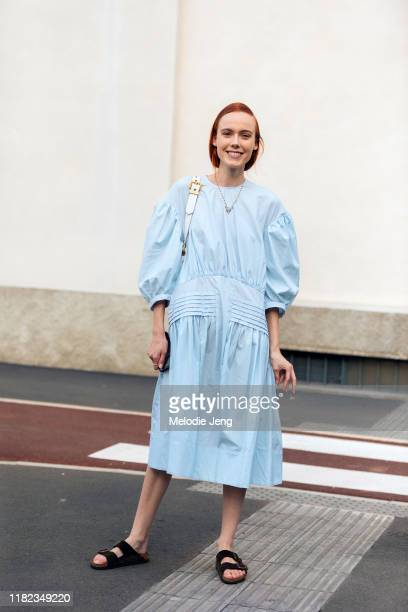 Model Kiki Willems wears a light blue oversized dress and brown Birkenstock sandals after the Prada show during Milan Fashion Week Spring/Summer 2020...