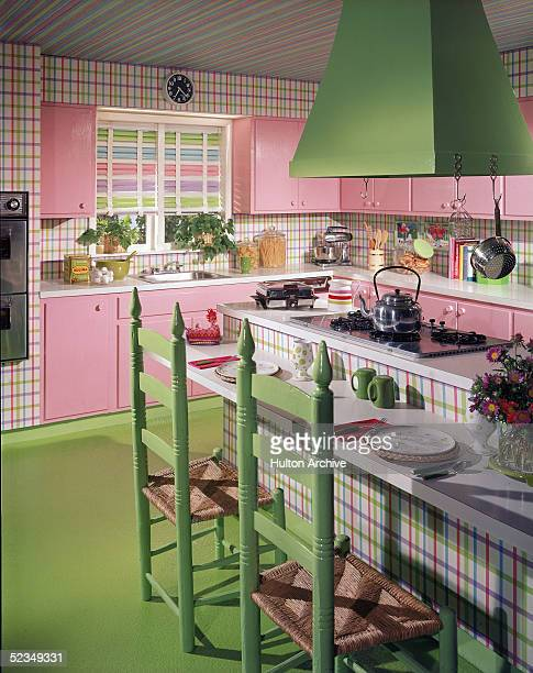 A model kitchen in pink and green with green red purple and blue plaid walls and ceiling features hooded stove a dining surface pink cabinets jars of...