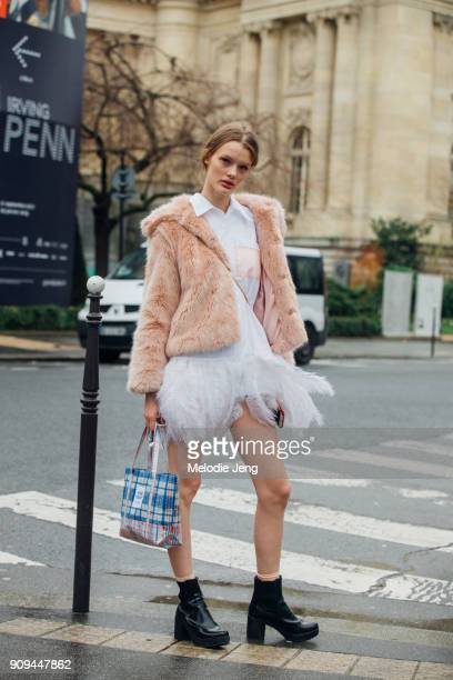 Model Kris Giskaite wears a light pink fur coat over a white Prada feather-trimmed shirt dress white dress and a plaid Opening Ceremony bag outside...