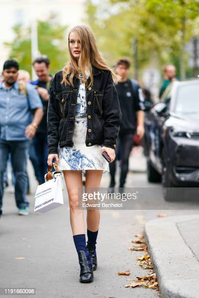 Model Kris Grikaite wears a black denim jacket, a white dress with blue printed drawings, navy blue socks, black leather shoes, outside Paco Rabanne,...