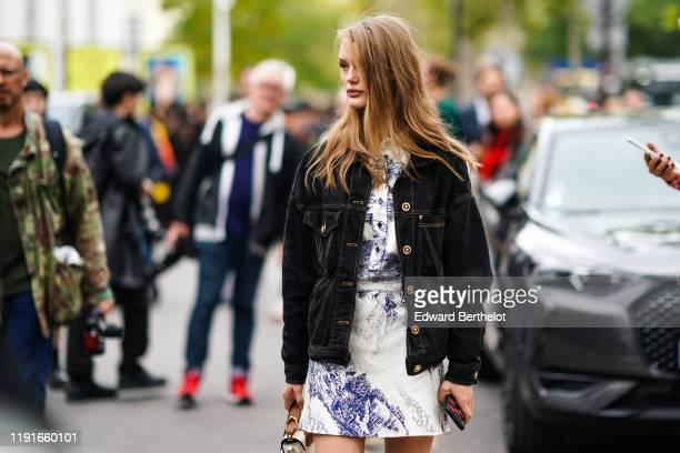 Model Kris Grikaite wears a black denim jacket, a white dress with blue printed drawings, outside Paco Rabanne, during Paris Fashion Week -...