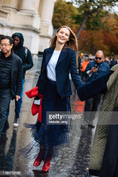 Model Kris Grikaite wears a blue blazer white shirt blue lace embroidered skirt and red boots after the Chanel show during Paris Fashion Week...