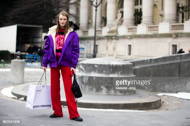 Model Kris Grikaite wears a purple Prada bomber jacket red sweater red sports trousers and holds a black Prada beltbag fanny pack on March 1 2018 in...