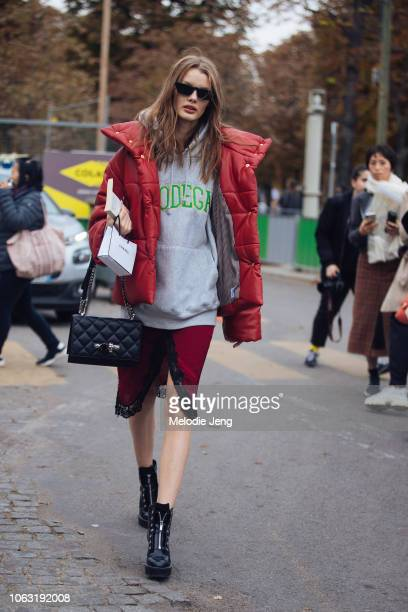 Model Kris Grikaite wears black sunglasses a red puffer jacket Bodega gray hoodie black skull purse red slip dress and black boots after the Chanel...