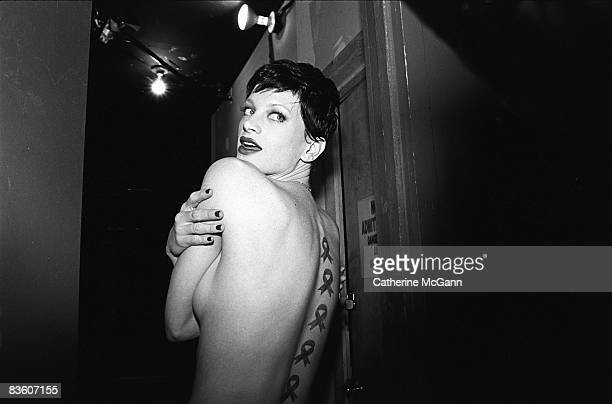 Model Kristen McMenamy poses for a photo and shows off the AIDS awareness ribbons painted on her back at an AmFar Benefit at Webster Hall in February...