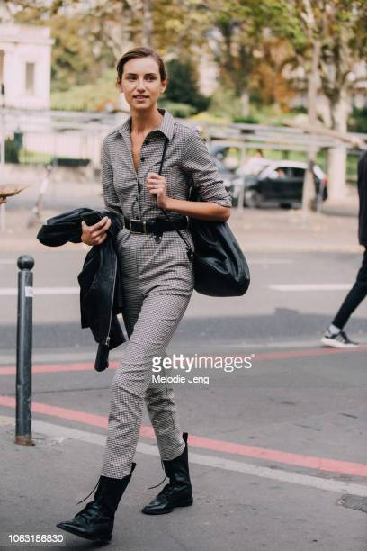 Model Ksenia Golubeva wears a gray patterned jumpsuit and black boots during Paris Fashion Week Spring/Summer 2019 on September 28 2018 in Paris...