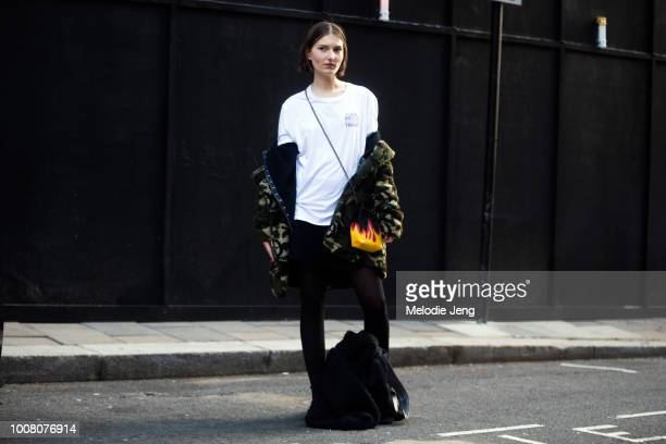 Model Lais Van Niel wears a white 'Fuck Trump' tshirt a green fur coat off her shoulders and a black flame purse on Day 4 of the London Fashion Week...