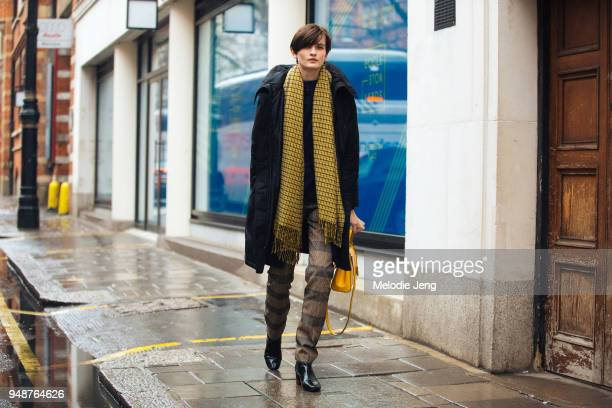 Model Lara Mullen wears a black winter coat yellow patterned scarf brown tartan pants black boots and a yellow purse during London Fashion Week...