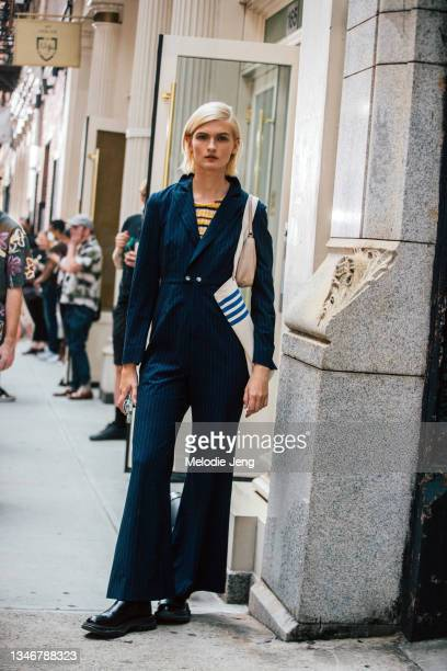 Model Lara Mullen wears a blue pinstripe jumpsuit, black boots, and carries a white Tory Sport tote bag after the Tory Burch show on September 12,...