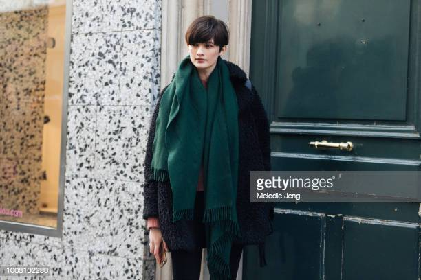 Model Lara Mullen wears a green scarf and fuzzy black coat after the Paul Smith show during Paris Men's Fashion Week Fall/Winter 2017 on January 22...