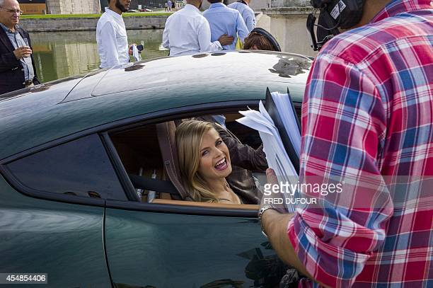 A model laughs while working with a member of a technical crew during the first edition of the Chantilly Arts and Elegance Richard Mille event on...